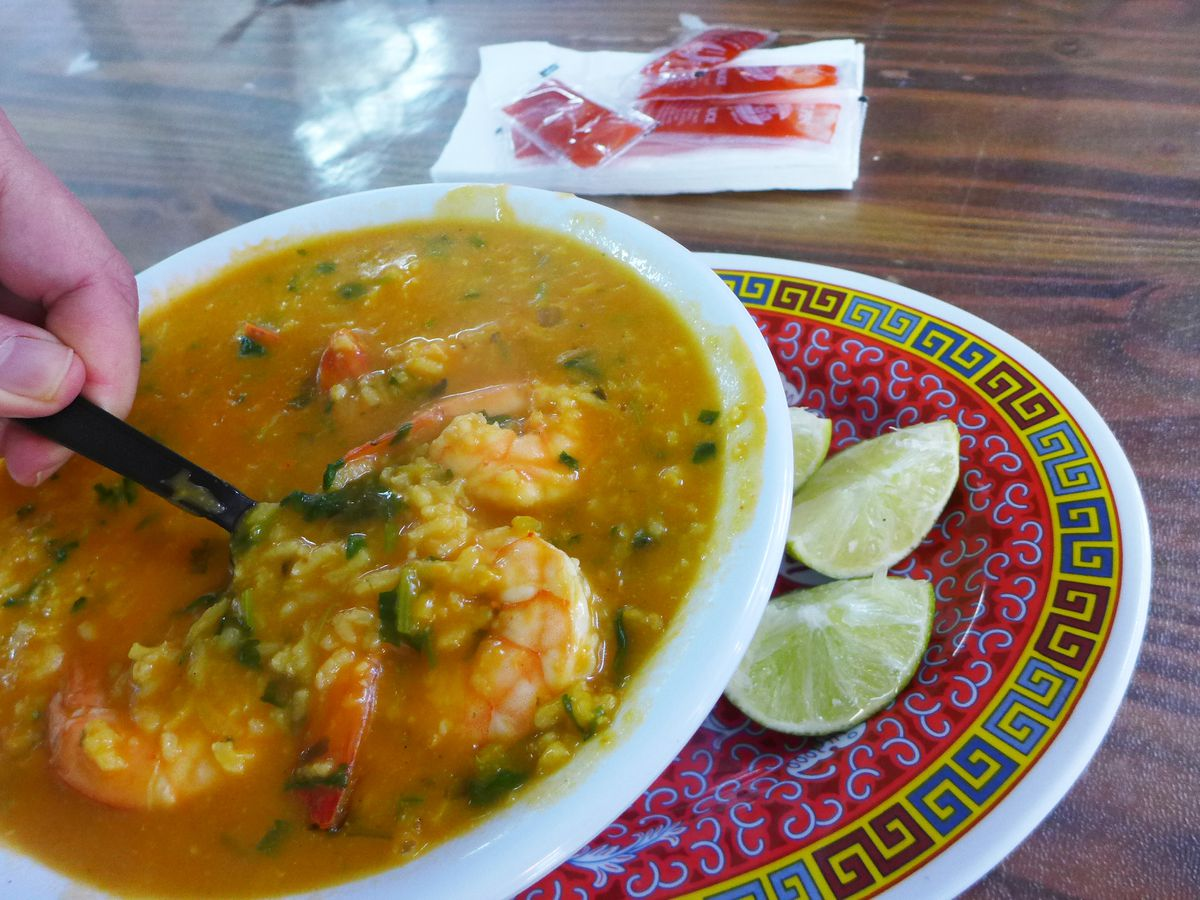 A hand lifts up a spoonful of red soup with shrimp.