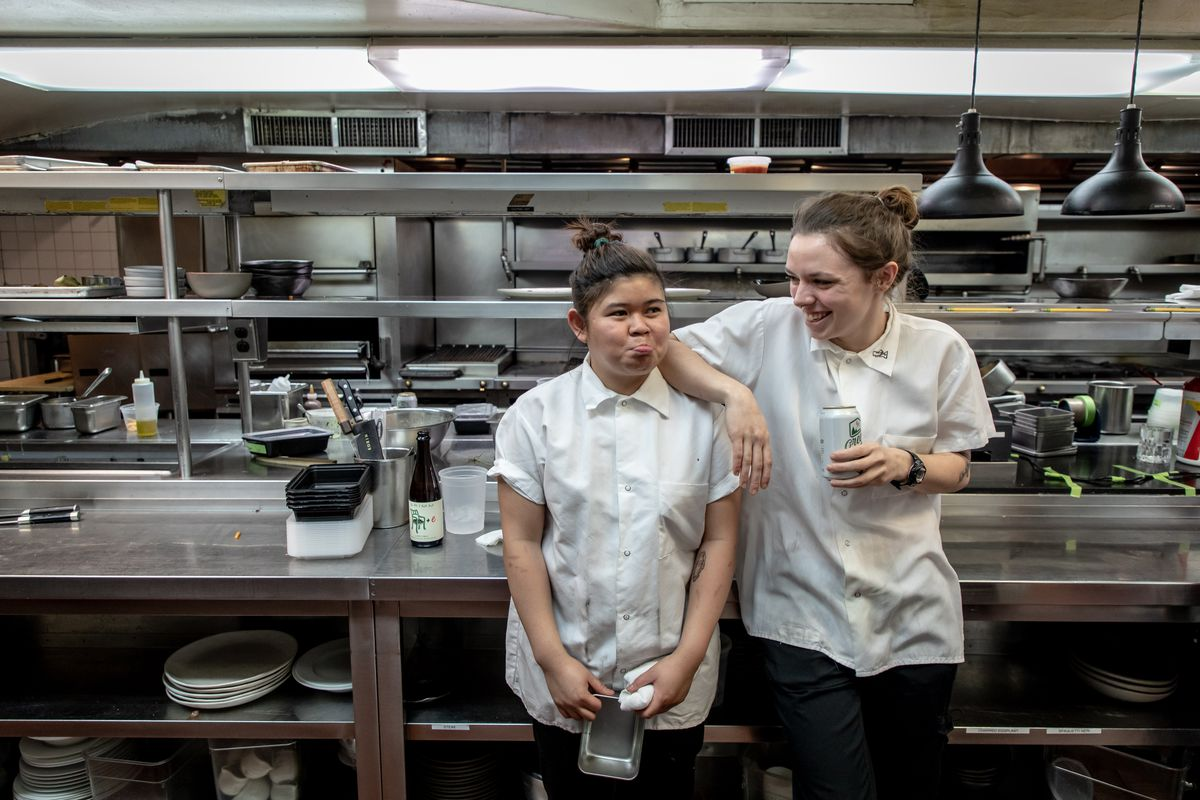 Two line cooks stand in the kitchen, with one resting her arm on the other.