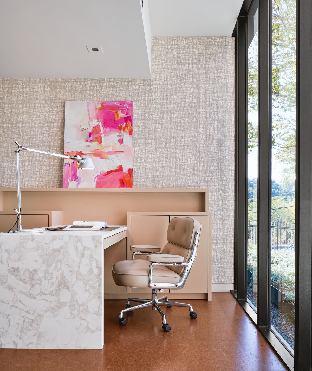 Photo of an office with a textured back wall, a modern credenza and rolling chair, and a rectangular desk extending to the credenza. There are floor-to-ceiling windows on the right size. There's a stainless steel task light on the desk and a painting propped on the credenza.
