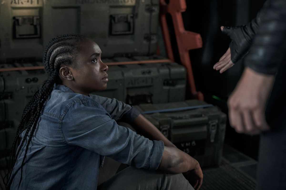 Kiki Layne sits amid weapons and ammo cases, glaring up at Charlize Theron in The Old Guard.