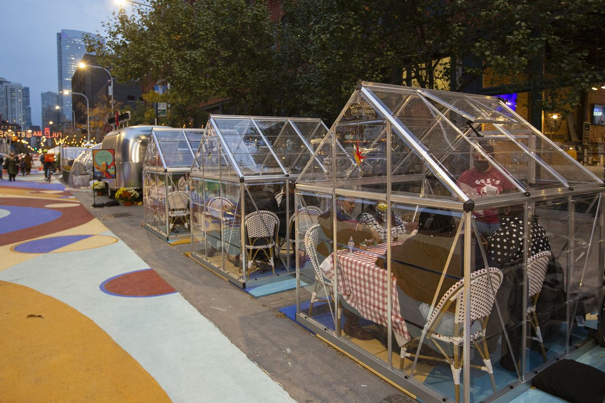 A greenhouse-like structure on the street where people are eating lunch.