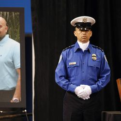 A Transportation Security Administration officer stand in front of a portrait of slain TSA officer Gerardo Hernandez during his public memorial at the Los Angeles Sports Arena, Tuesday, Nov. 12, 2013. Hernandez was the first TSA officer killed in the line of duty when a gunman pulled a rifle from a bag and shot the 39-year-old father of two on Nov. 1 at Los Angeles International Airport. Two other TSA officers and a teacher were injured before airport police wounded the gunman, Paul Ciancia.