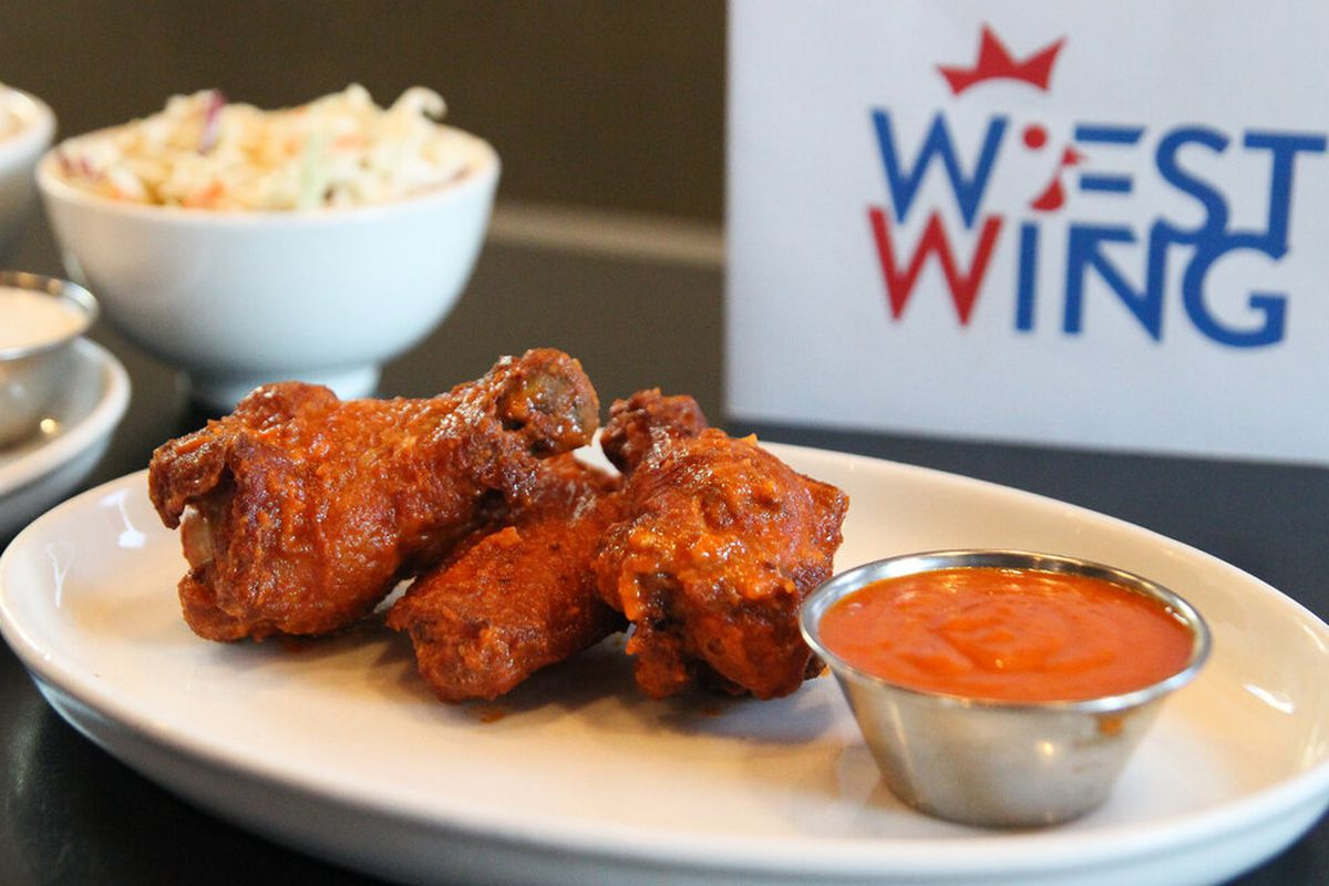 """A plate of Buffalo wings with a side of sauce, mac salad, and a sign that says """"West Wing"""" in the background"""