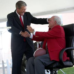 """Athletics Director Chis Hill presents Spencer F. Eccles with a football and office chair for """"Coach Eccles"""" at the grand opening of the new Spence and Cleone Eccles Football Center at the University of Utah in Salt Lake City on Thursday, Aug. 15, 2013."""