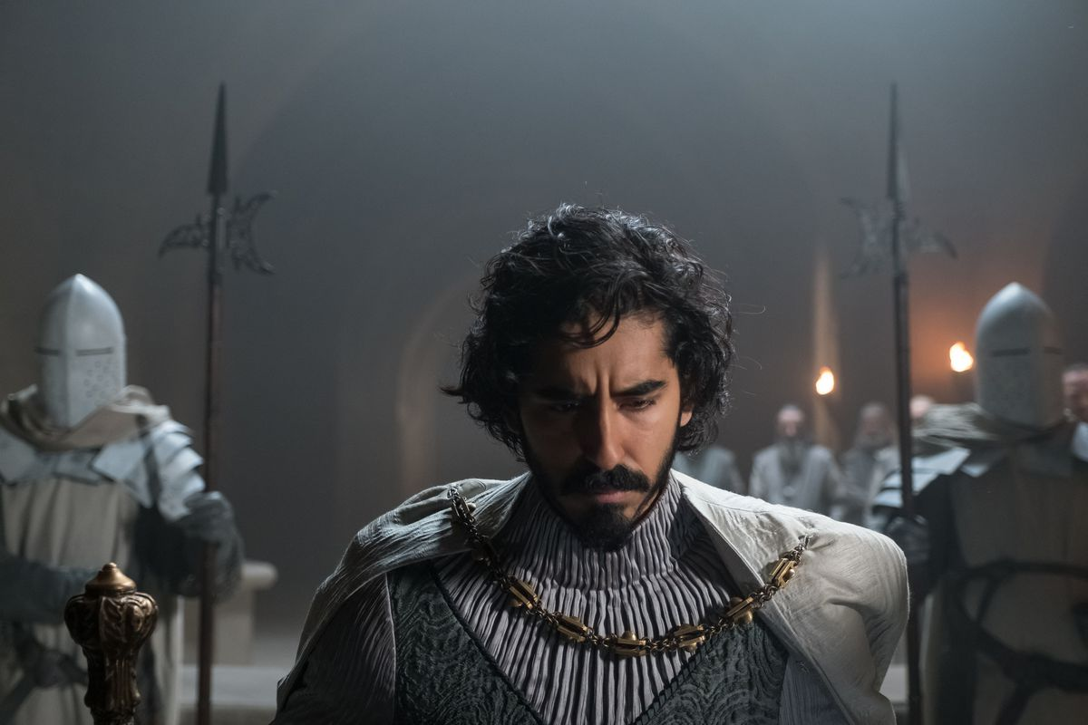 Patel in armor looks down, flanked by soldiers on the sides.