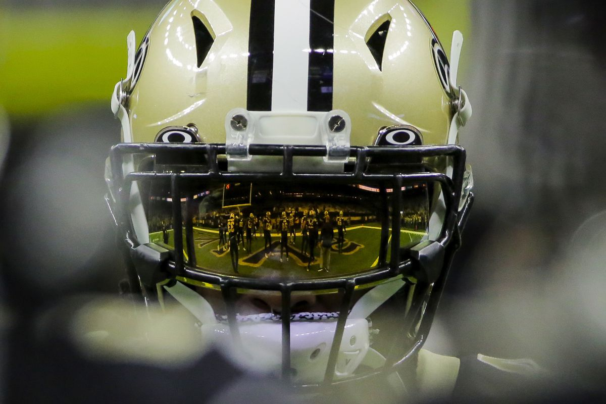A reflection of players huddling is seen on the visor of New Orleans Saints running back Alvin Kamara prior to kickoff against the Carolina Panthers at the Mercedes-Benz Superdome.