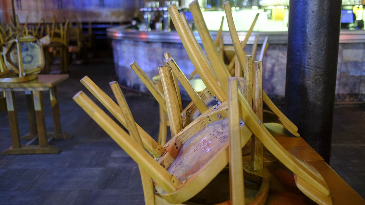Wooden chairs appear stacked on a bar alongside a window in a closed restaurant.