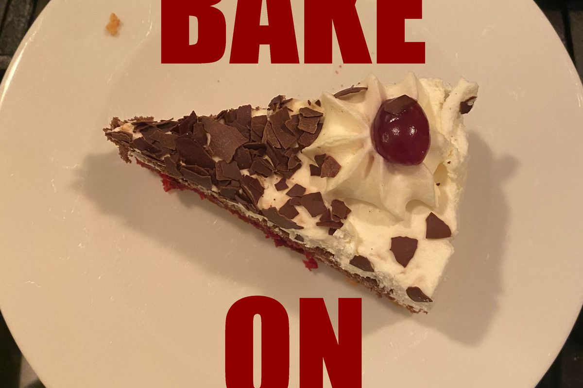 The words BAKE ON in dark red are superimposed over a photograph of a slice of cake on a white, round plate. The cake has white icing, shaved chocolate, and a cherry on top.