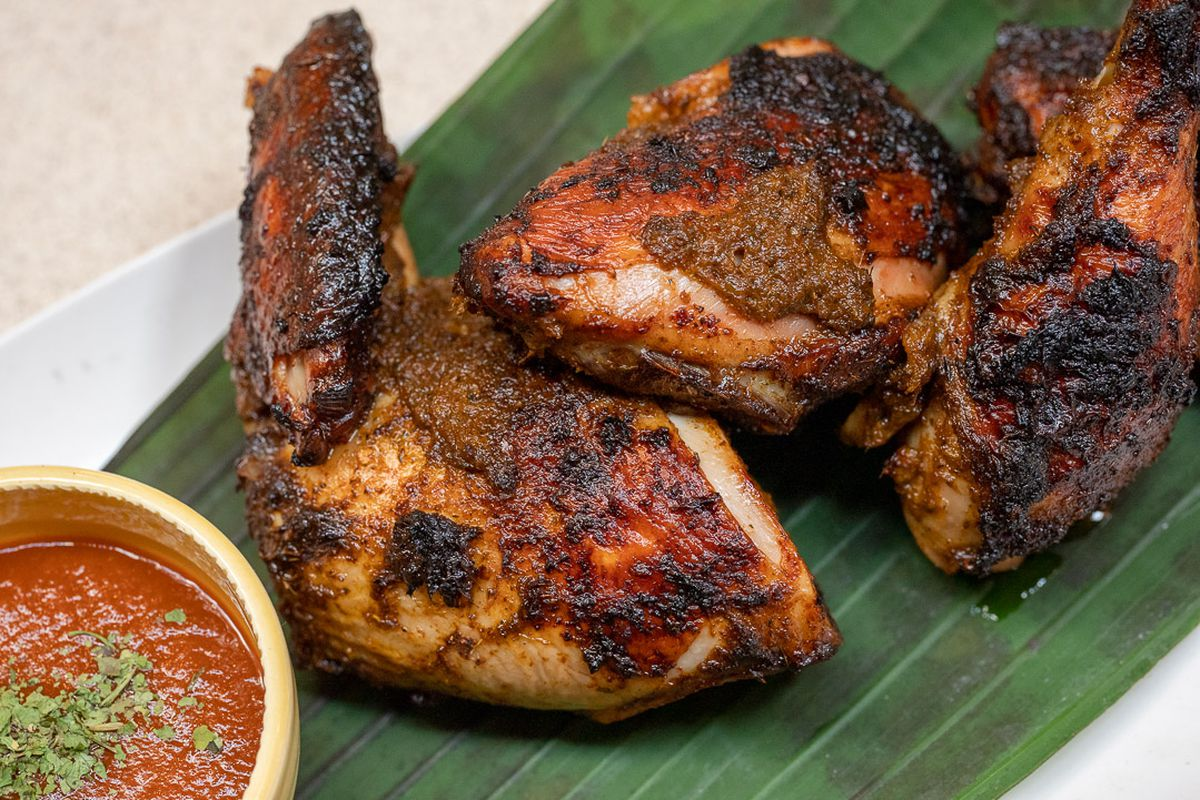 Three pieces of dark-roasted chicken on a large green leaf next to a bowl of reddish sauce with green sprinkled leaves.