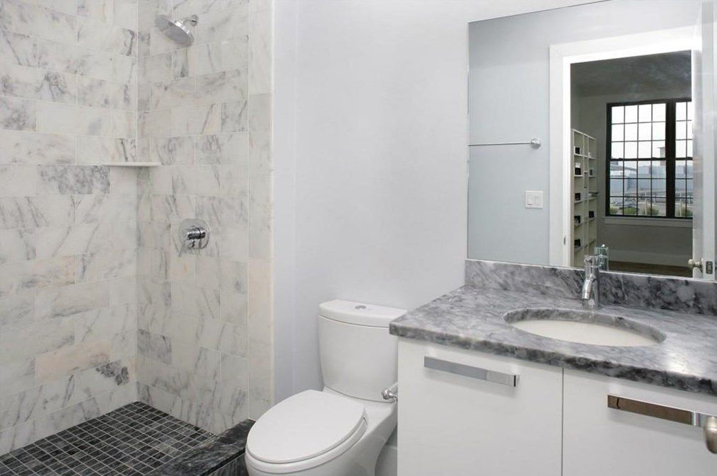 A sleek, marbled bathroom with no covering on the shower.
