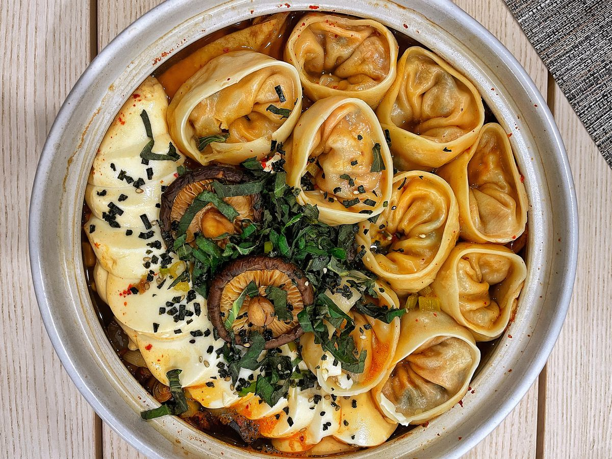 Round dumplings in a hot pot with rice cakes, mushrooms, herbs, and broth.