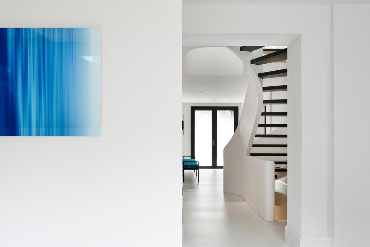 A blue artwork hangs on a white wall, while a white curving staircase is in the distance.