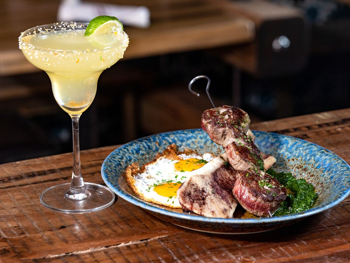 blue plate with skewered meat and sunny side up eggs next to a margarita