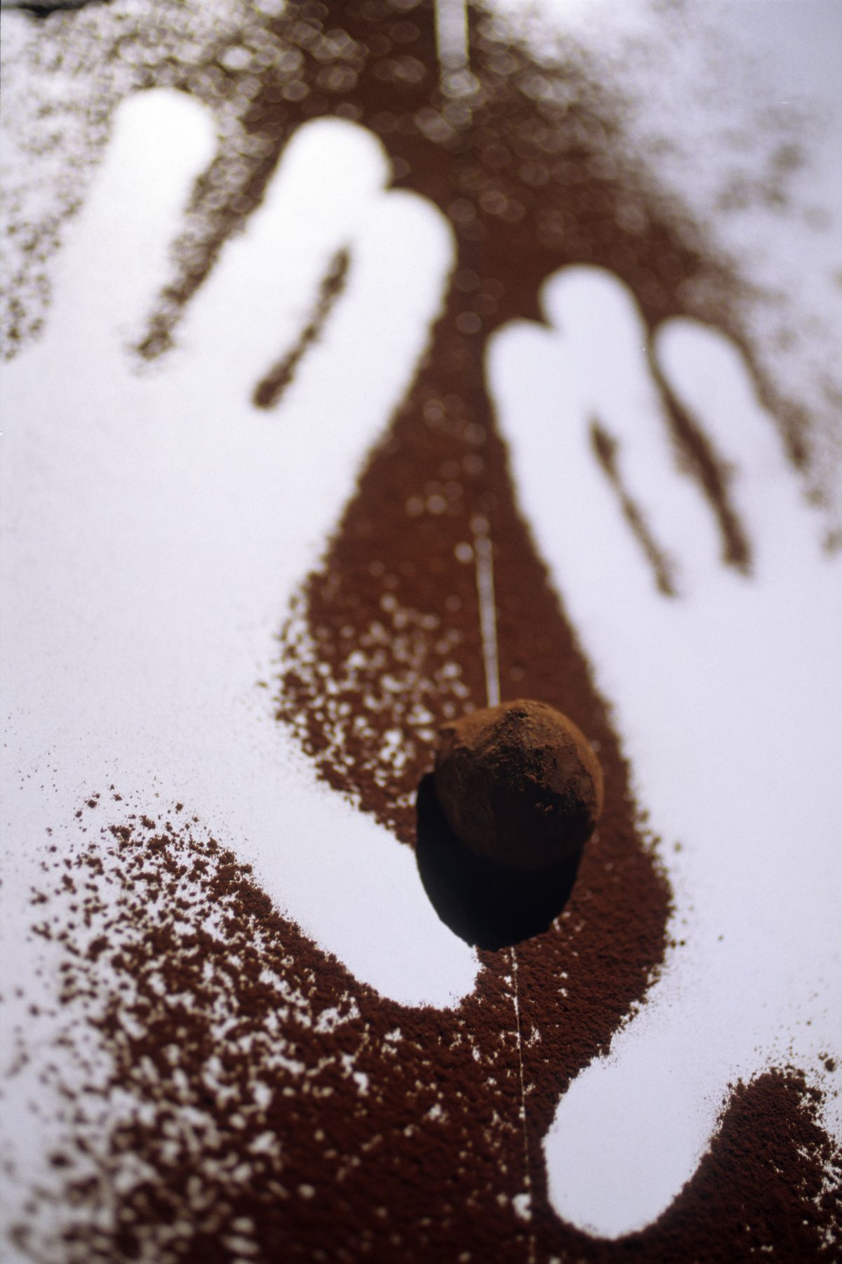 chocolate truffle flanked by outlines of hands in cocoa powder