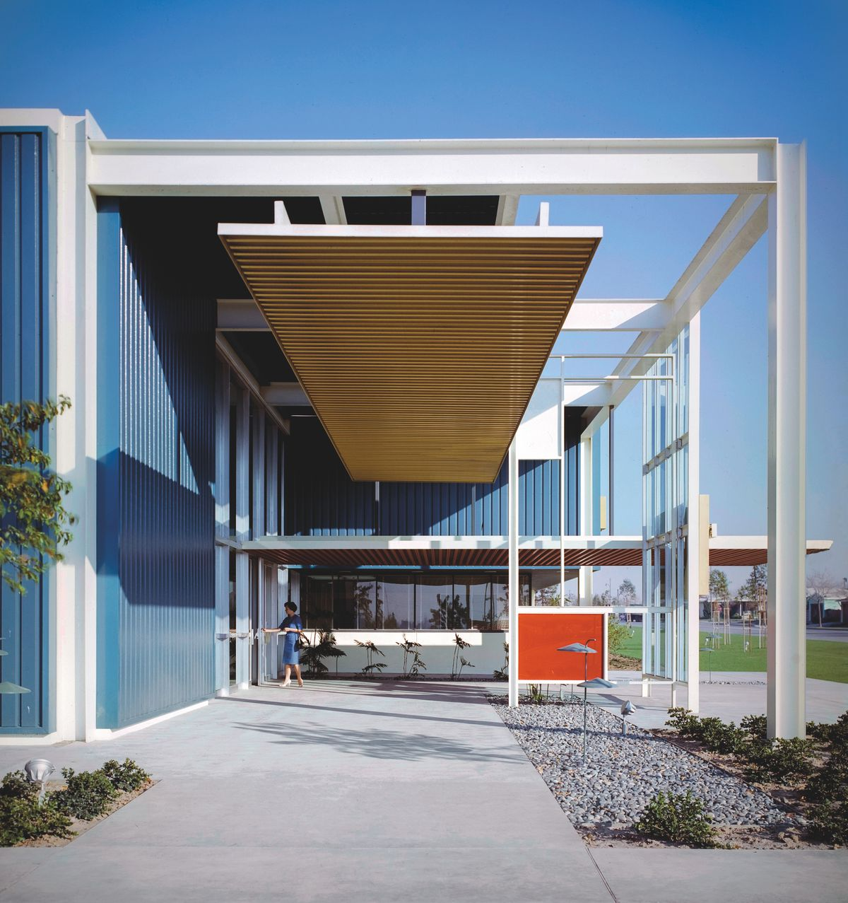 A boxy midcentury office building with blue walls and white-painted framing.