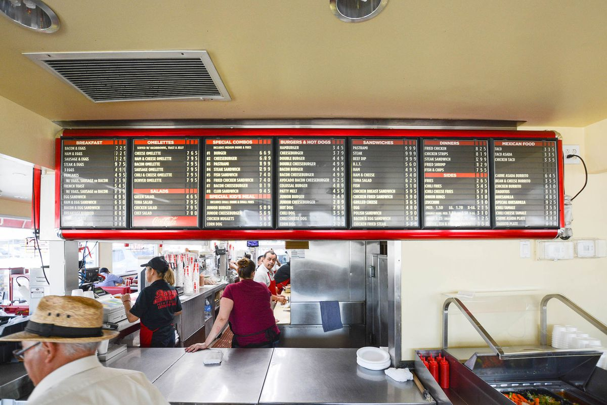 The inside of a drive thru restaurant complete with old school menu board.