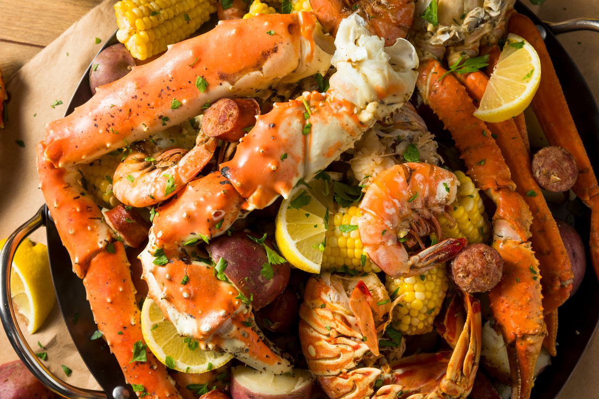 A homemade Cajun seafood boil with lobster, crab, and shrimp and slices of lemon.