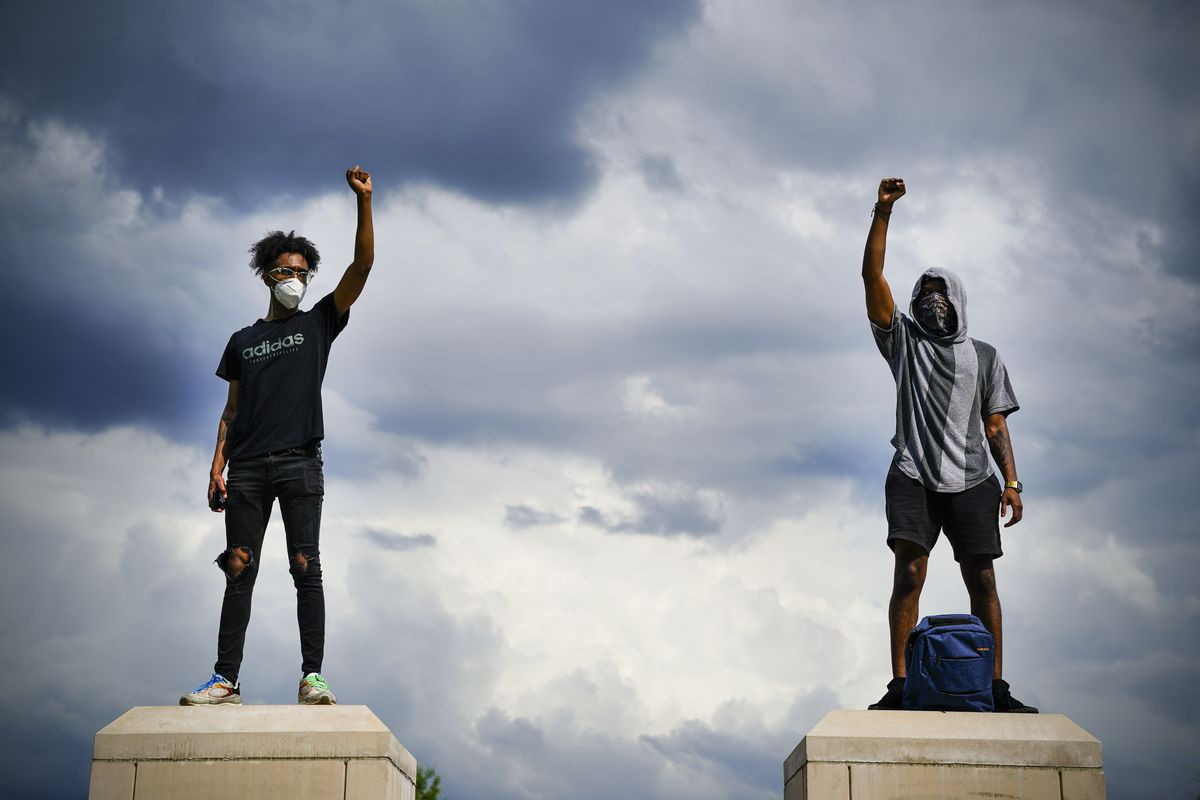 Two masked black men raise their fists against a stormy sky.