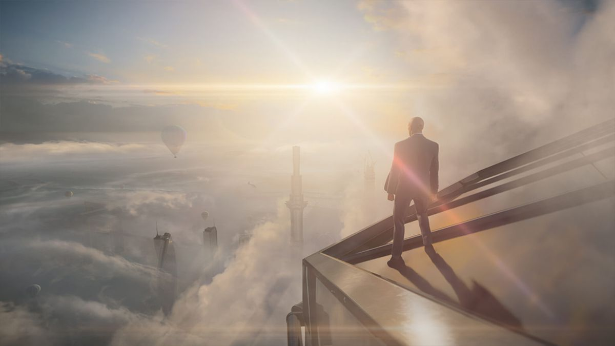 Agent 47 stands in the clouds atop a Dubai skyscraper in Hitman 3