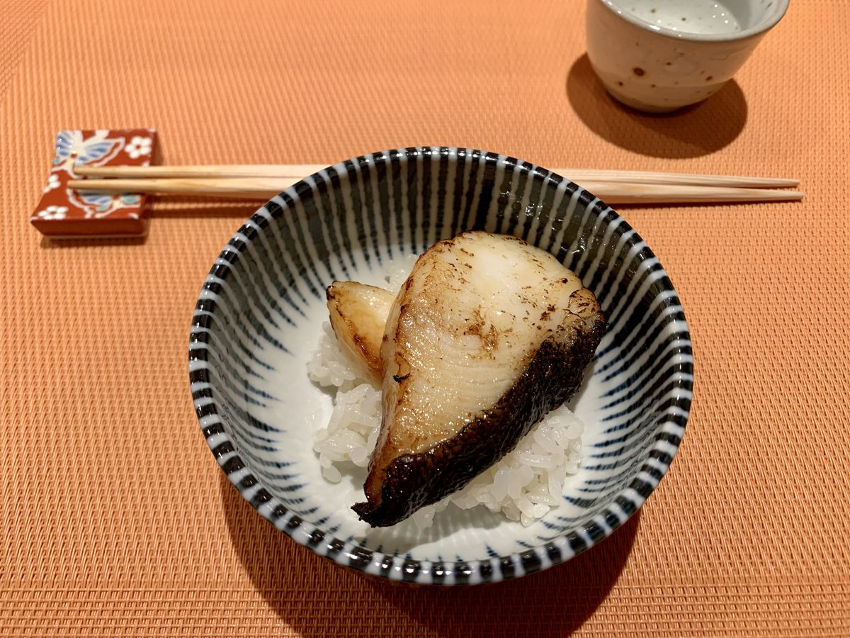 Two pieces of broiled cod on top of white rice in a small blue and white bowl