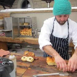 A cook from 8100 assembles Pig Burgers at the Aprés-Ski Burger and Beers event. The burger was topped with pulled porky goodness, cobb smoked bacon, jalapeño jam and pickled okra.