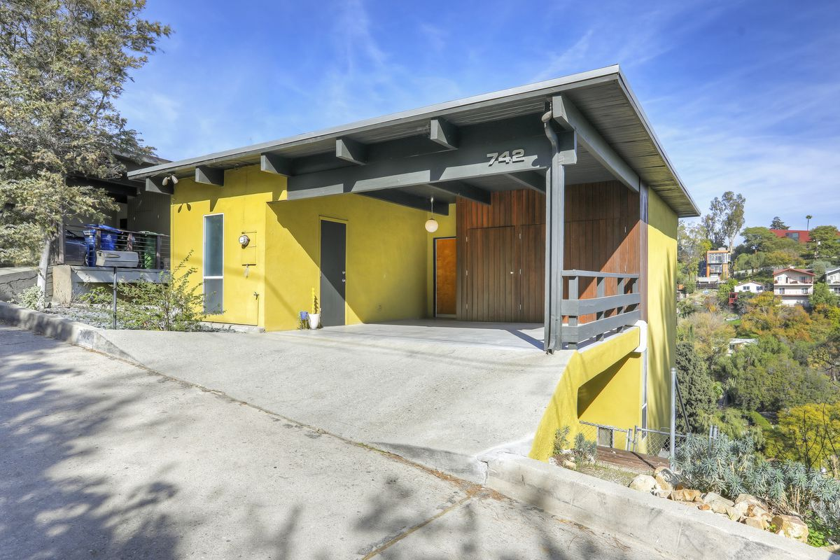 A yellow-colored, boxy house with an attached gray-colored carport.