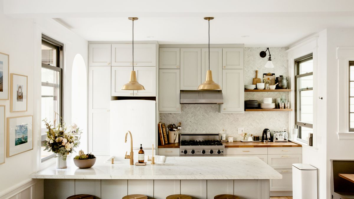 Bright kitchen with a marble-topped island, brass fixtures, and wooden countertops and shelves.