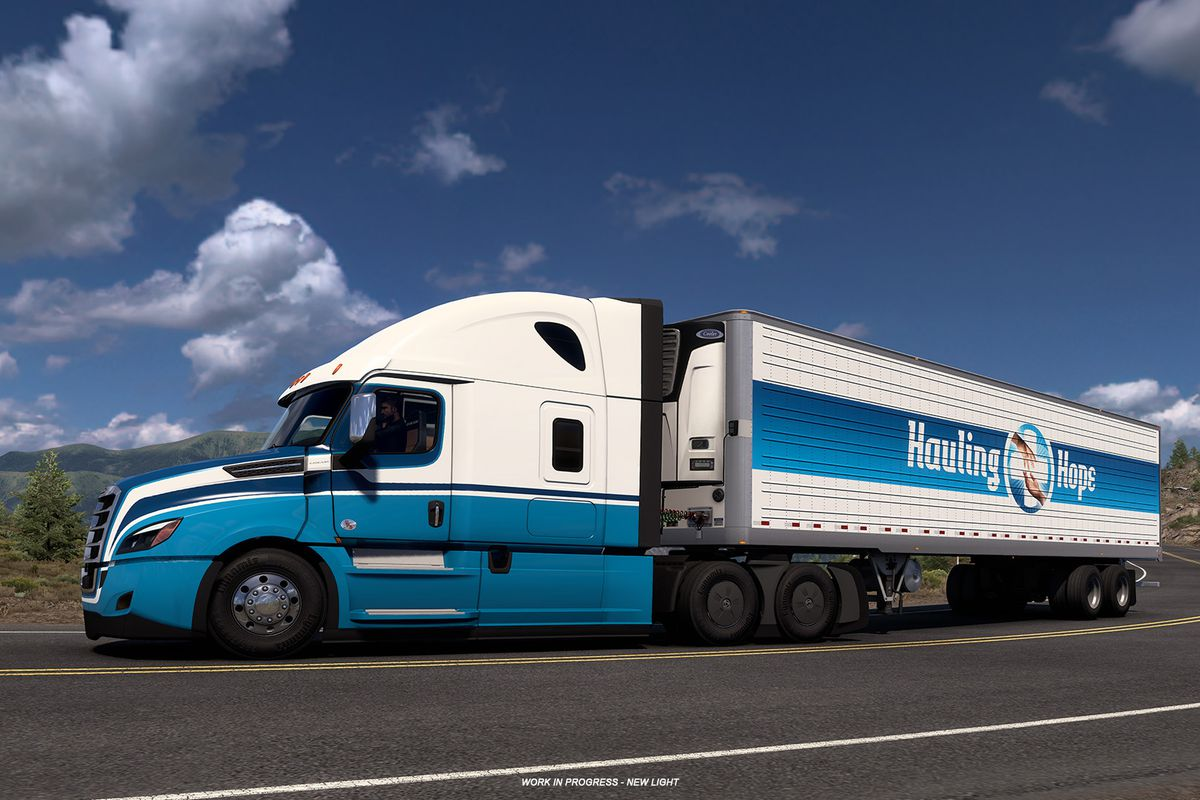 a white truck with a blue logo on the trailer that says Hauling Hope drives underneath a partly cloudy blue sky