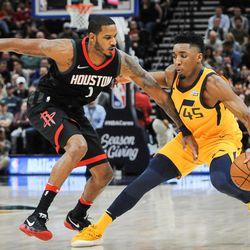 Utah Jazz guard Donovan Mitchell (45) dribbles around Houston Rockets forward Trevor Ariza (1) as the Utah Jazz host the Houston Rockets at Vivint Smart Home Arena in Salt Lake City on Thursday, Dec. 7, 2017.