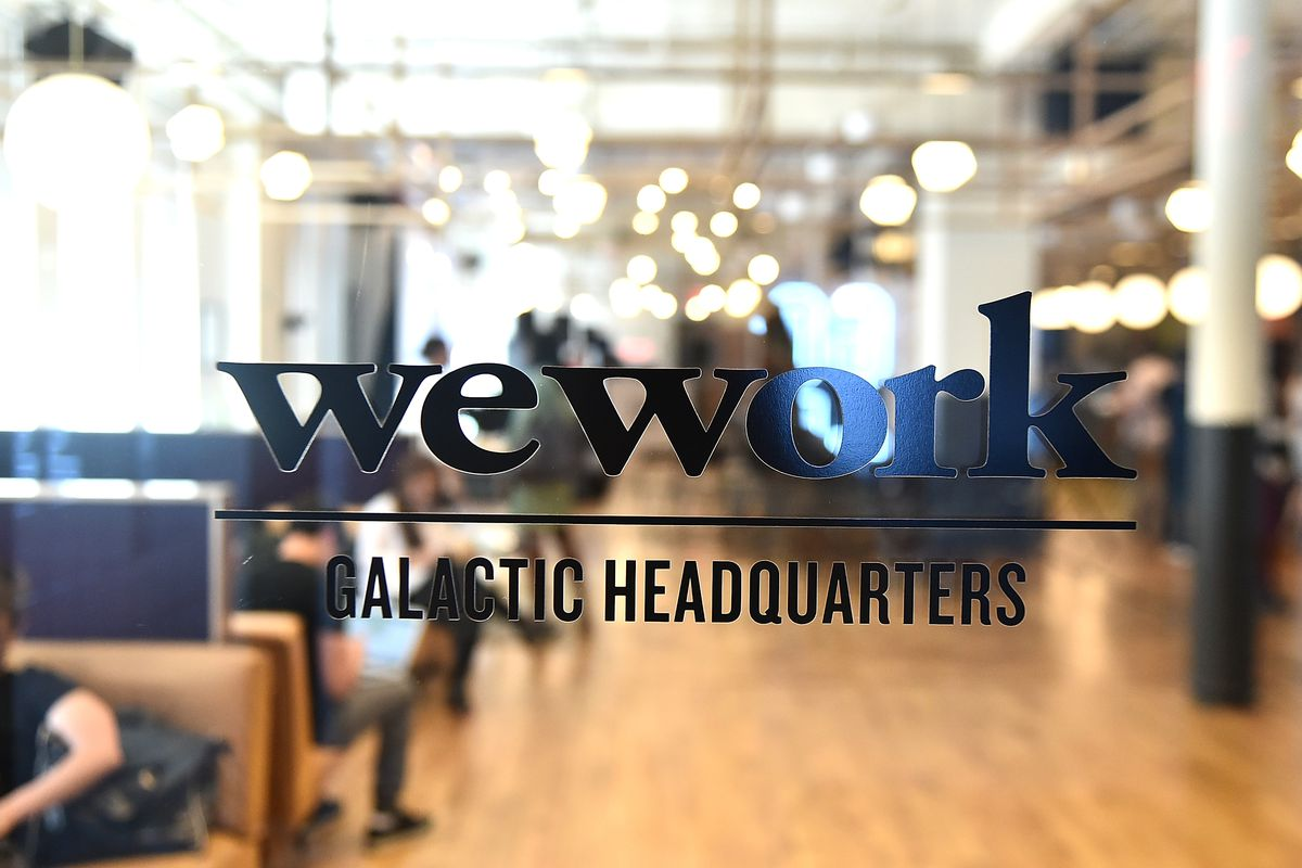 WeWork's logo on its glass front door, showing an office behind it