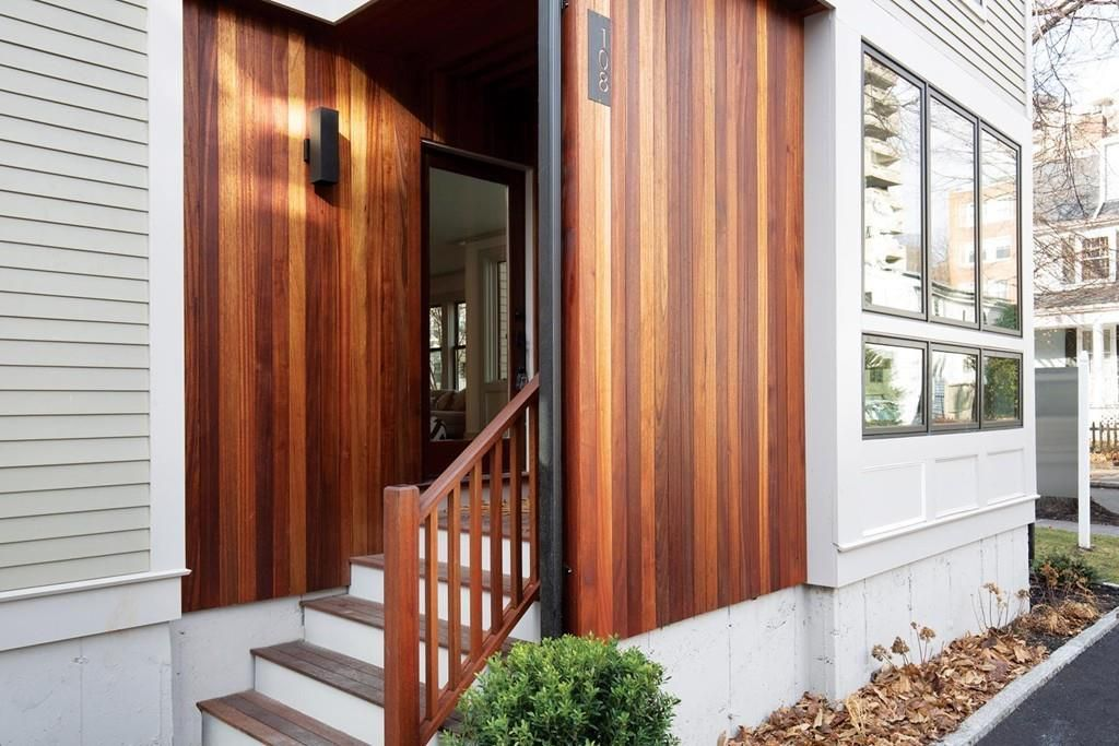 The mahogany wood entrance of a townhouse, with a few narrow steps leading to the door.
