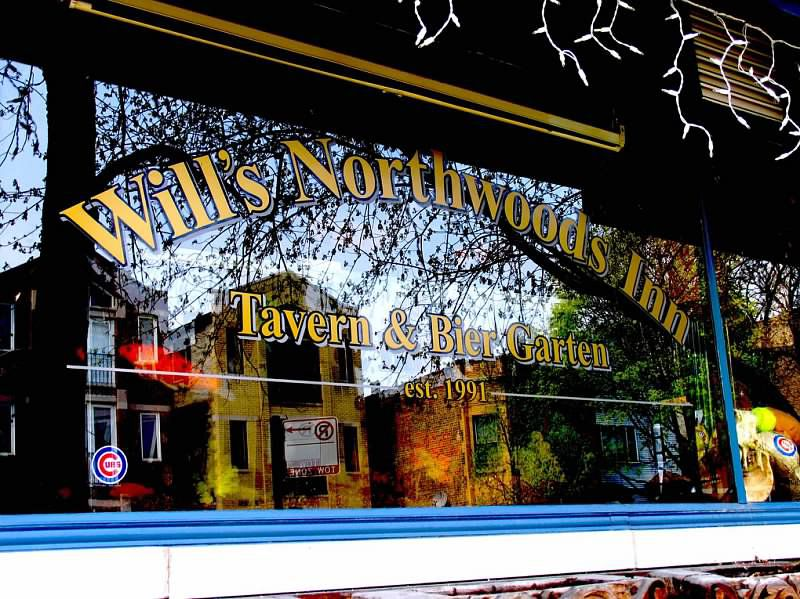 """A plate-glass window in front of the bar reads """"Will's Northwoods Inn Tavern and Bier Garden, est. 1991"""" in yellow letters with black outlines. A small Cubs sticker is visible on the window below the letters."""