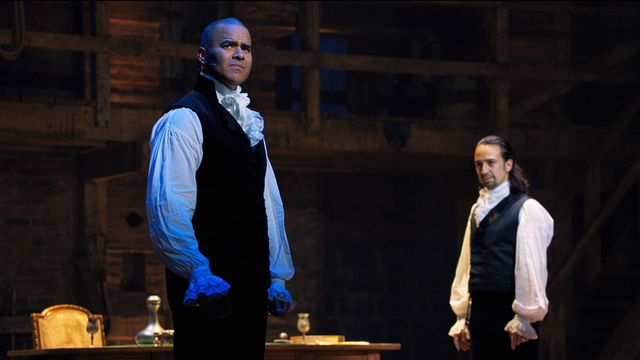 George Washington (Christopher Jackson) looks out into the audience while Hamilton (Lin-Manuel Miranda) watches him