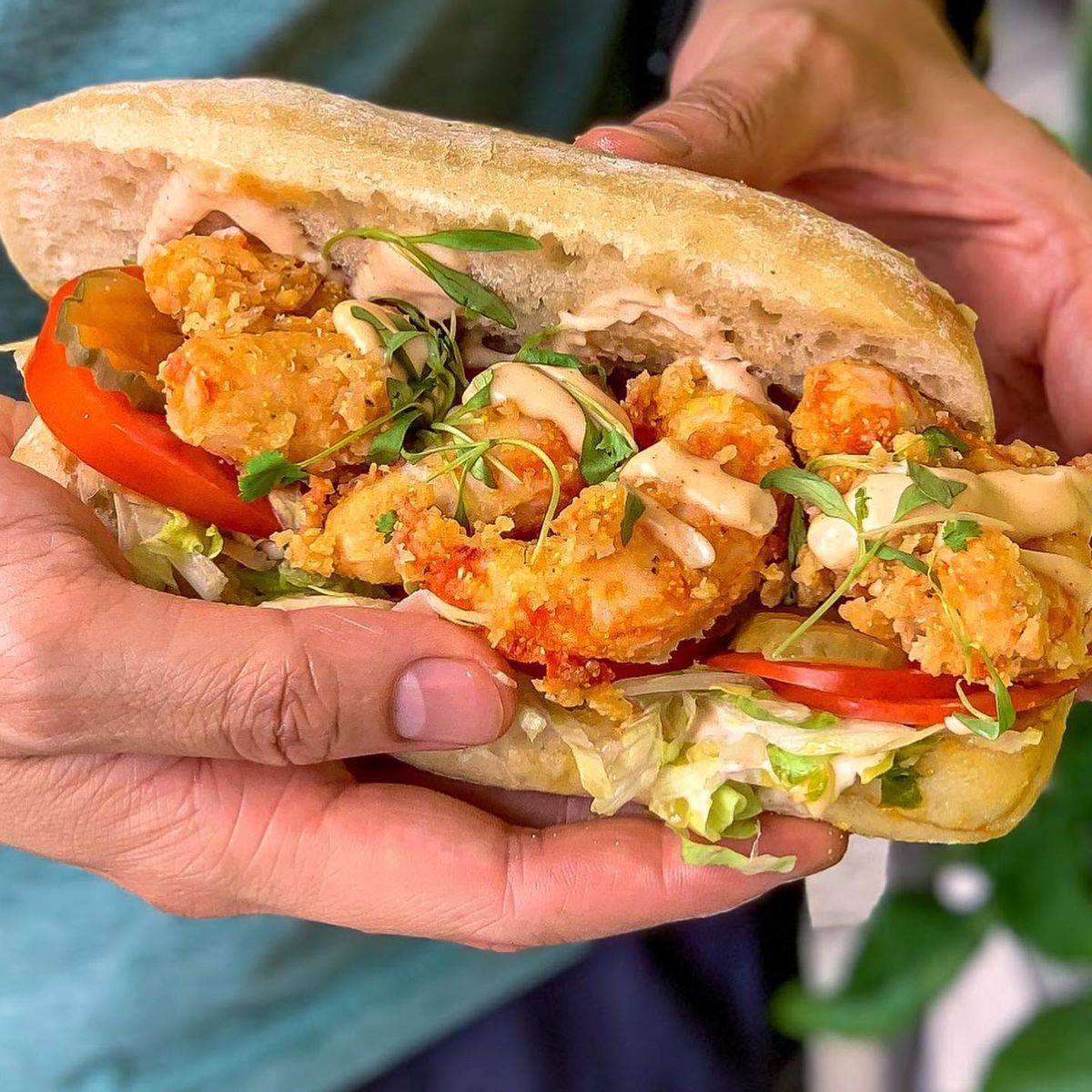 A vegan shrimp po' boy stuffed with fried shrimp, slices of red tomato, and shredded lettuce. Two hands are holding the sandwich.