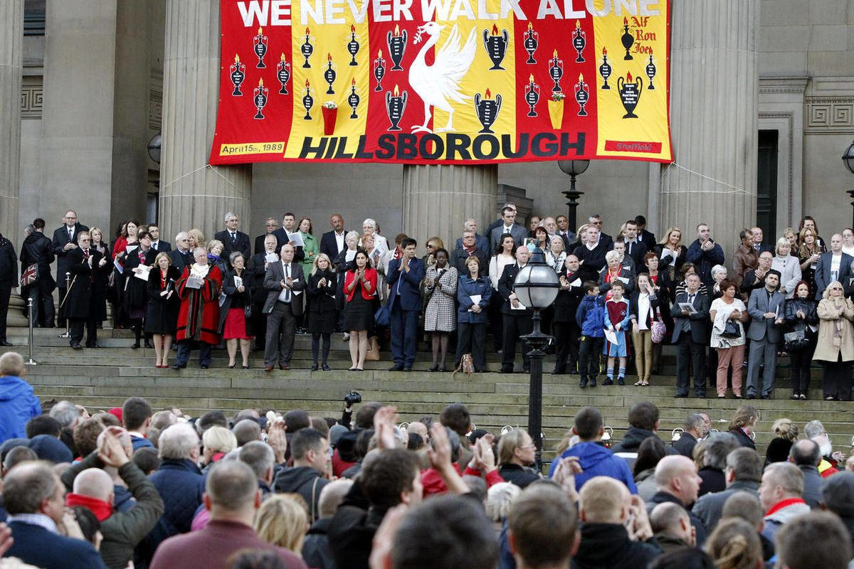 People gather at St George's Place to attend a vigil in memory of the 96 victims of the Hillsborough stadium disaster in Liverpool, England, Sept. 12, 2012. British police and medics whose failures contributed to the deaths of 96 soccer fans in the countr