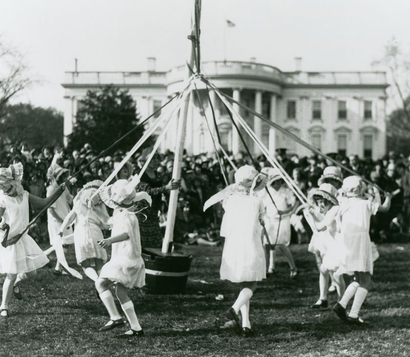Children dance around a maypole at the White House Easter Egg Roll, ca. 1930.