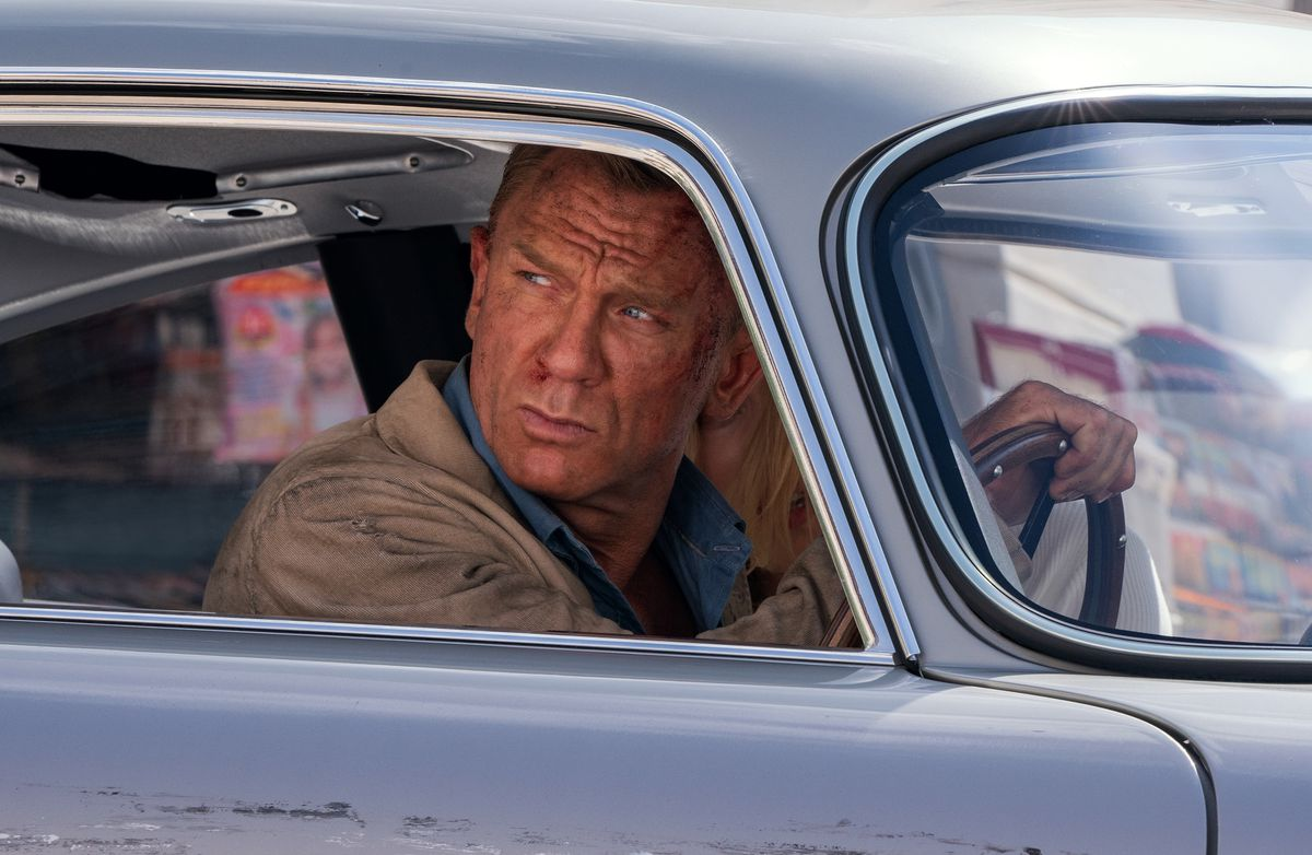 daniel craig's james bond, scratched and blood coming out of his nose, hunches over in the driver's seat of a British sports car