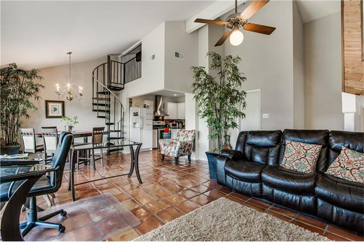 Condo living room with spiral stair at rear, lack leather couch.