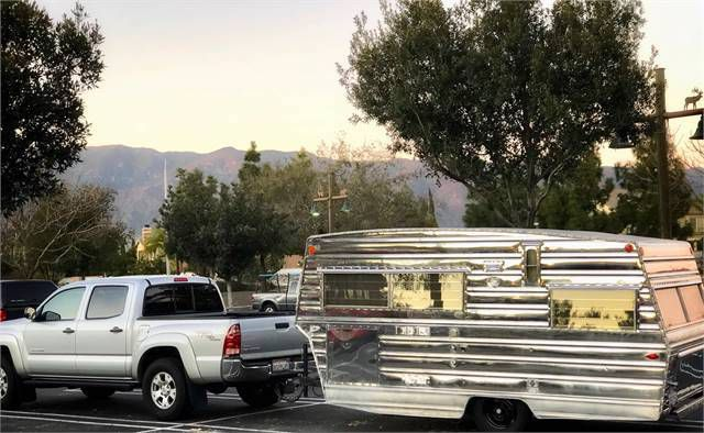 A silver camper trailer attached to a grey jeep.