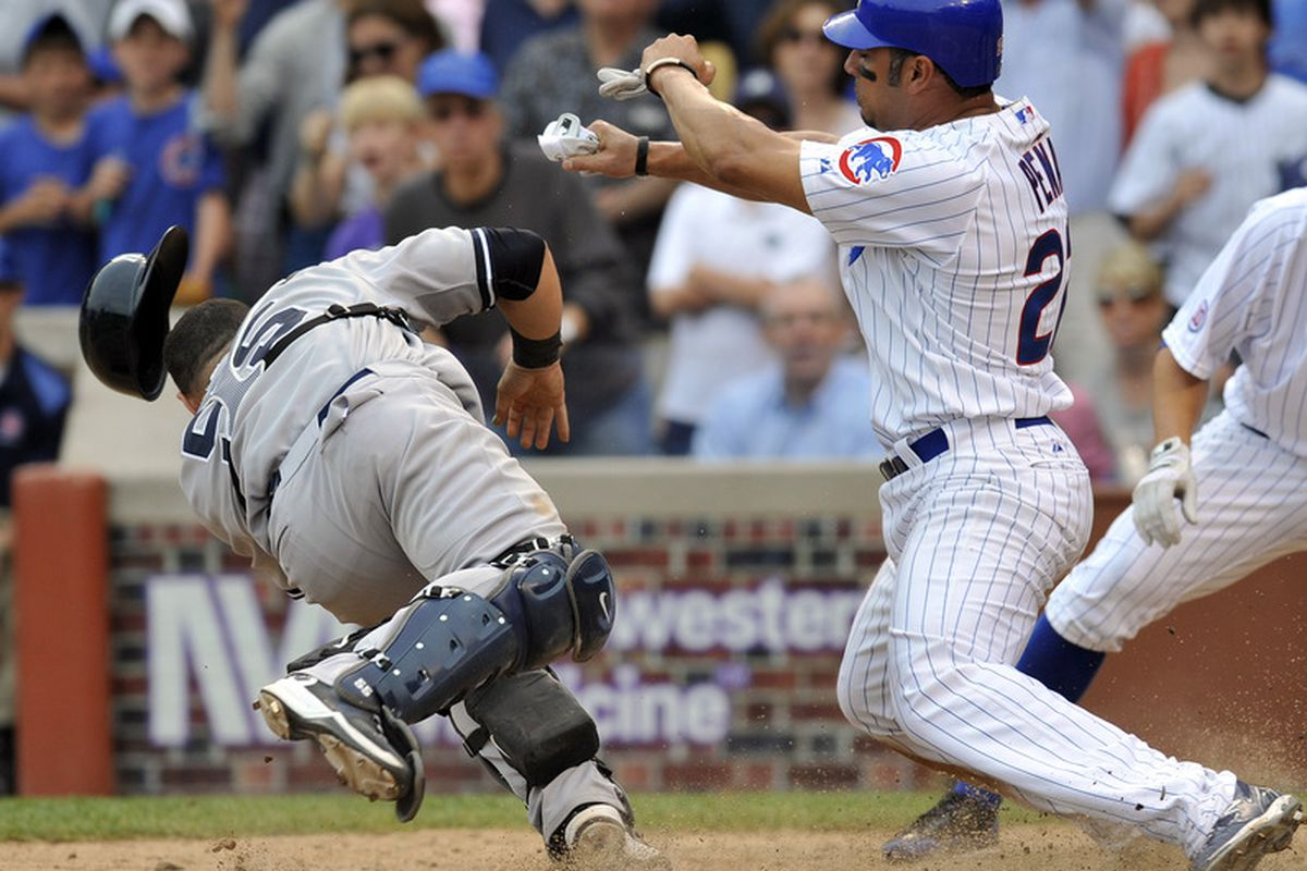 Carlos Pena of the Chicago Cubs is tagged out at home by Russell Martin of the New York Yankees on June 18, 2011 at Wrigley Field in Chicago, Illinois.  (Photo by David Banks/Getty Images)