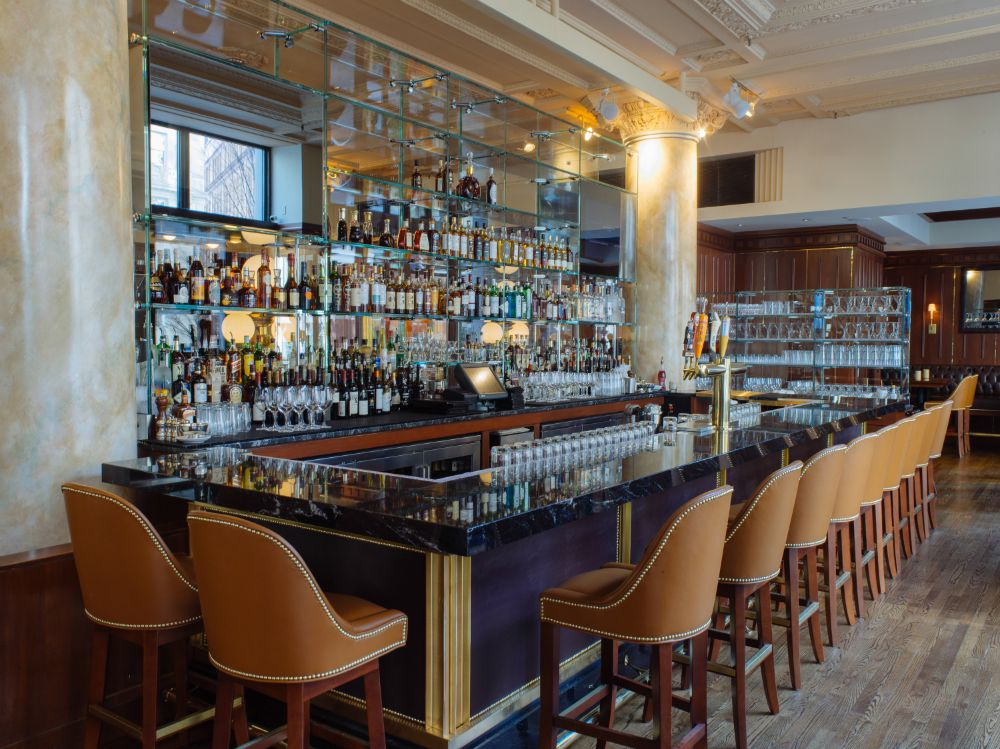 The bar at Grill 23, featuring marble columns, brown chairs, and light accents
