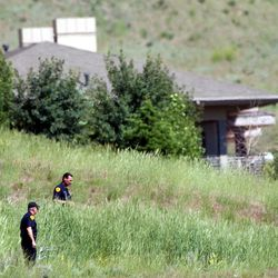 Two police offices search the area near the Smart family home in Federal Heights Wednesday, June 5, 2002 looking for clues in the abduction of 14-year-old Elizabeth Smart.