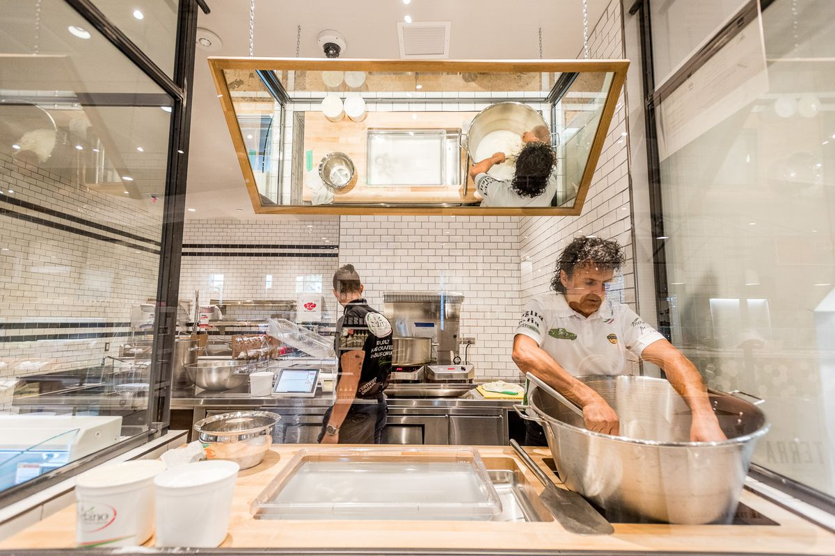 A worker makes fresh cheese under white lights at Eataly in Century City.