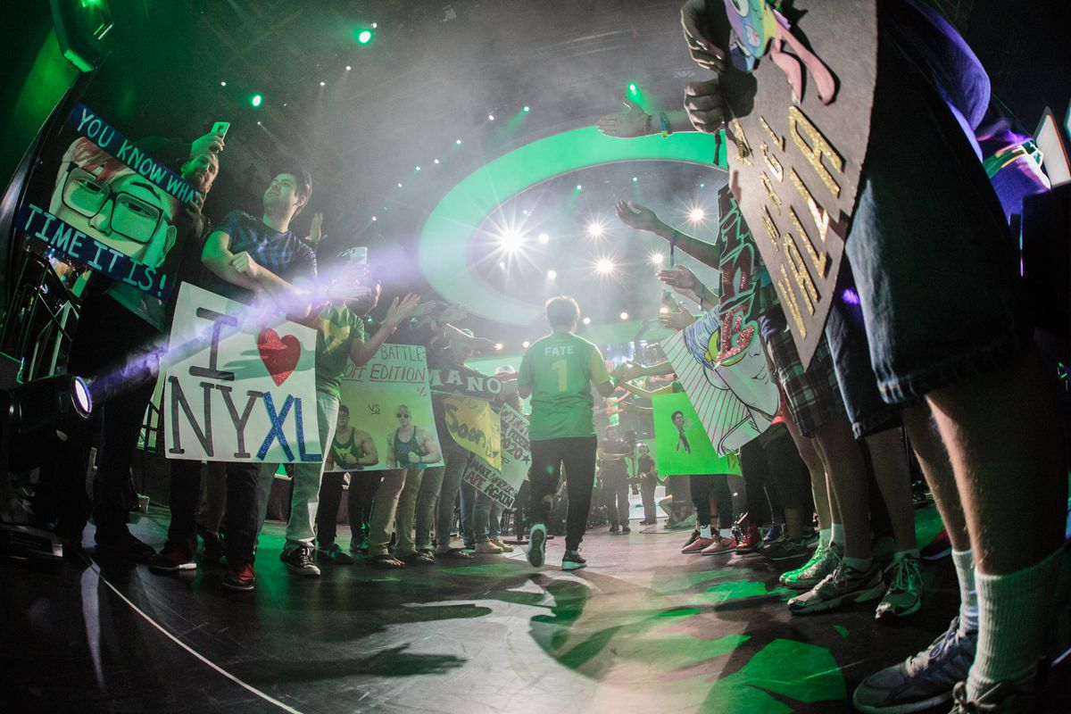 Overwatch League - a player from the Los Angeles Valiant enters the Blizzard Arena, surrounded by cheering fans.