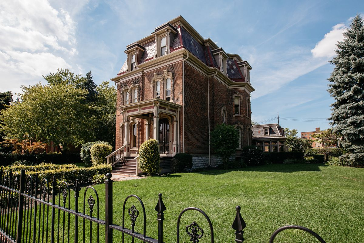 A three-story brick home with mansard roof. A black metal fence wraps around a large, grassy yard.