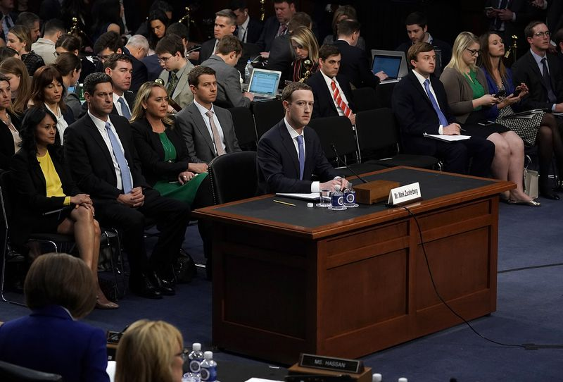 Facebook CEO Mark Zuckerberg sits and waits to provide testimony to Congress while reporters and observers fill the chairs behind him.