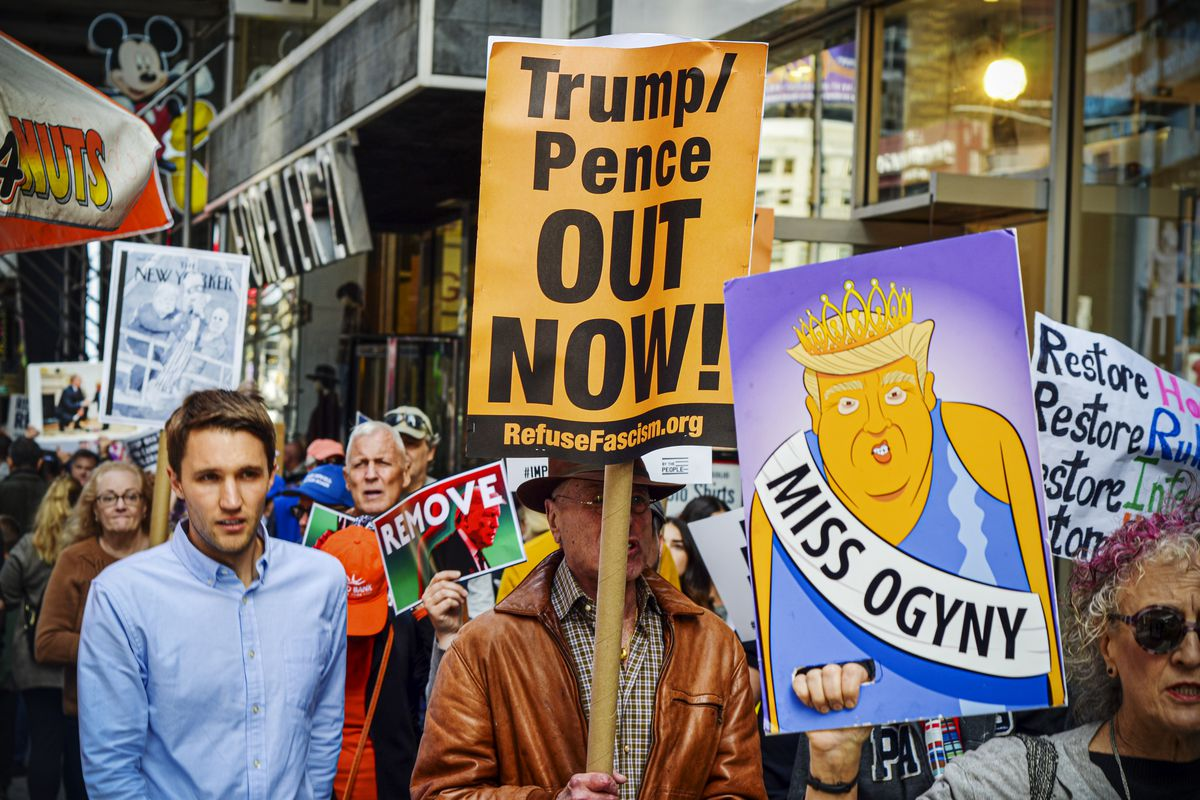 "Signs read, ""Miss Ogyny"" over a cartoon of Trump and ""Trump/Pence out now!"""