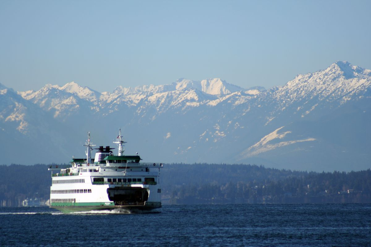A ferry operating on open water with mountains in the background.