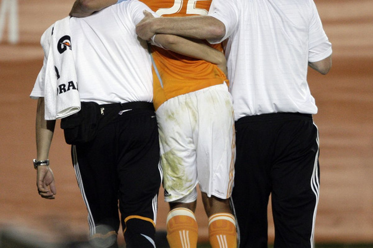 HOUSTON - APRIL 01:  Brian Ching #25 of the Housto Dynamo is assisted off the field by medical staff after injuring his left hamstring against Real Salt Lake on April 1, 2010 in Houston, Texas.  (Photo by Bob Levey/Getty Images)