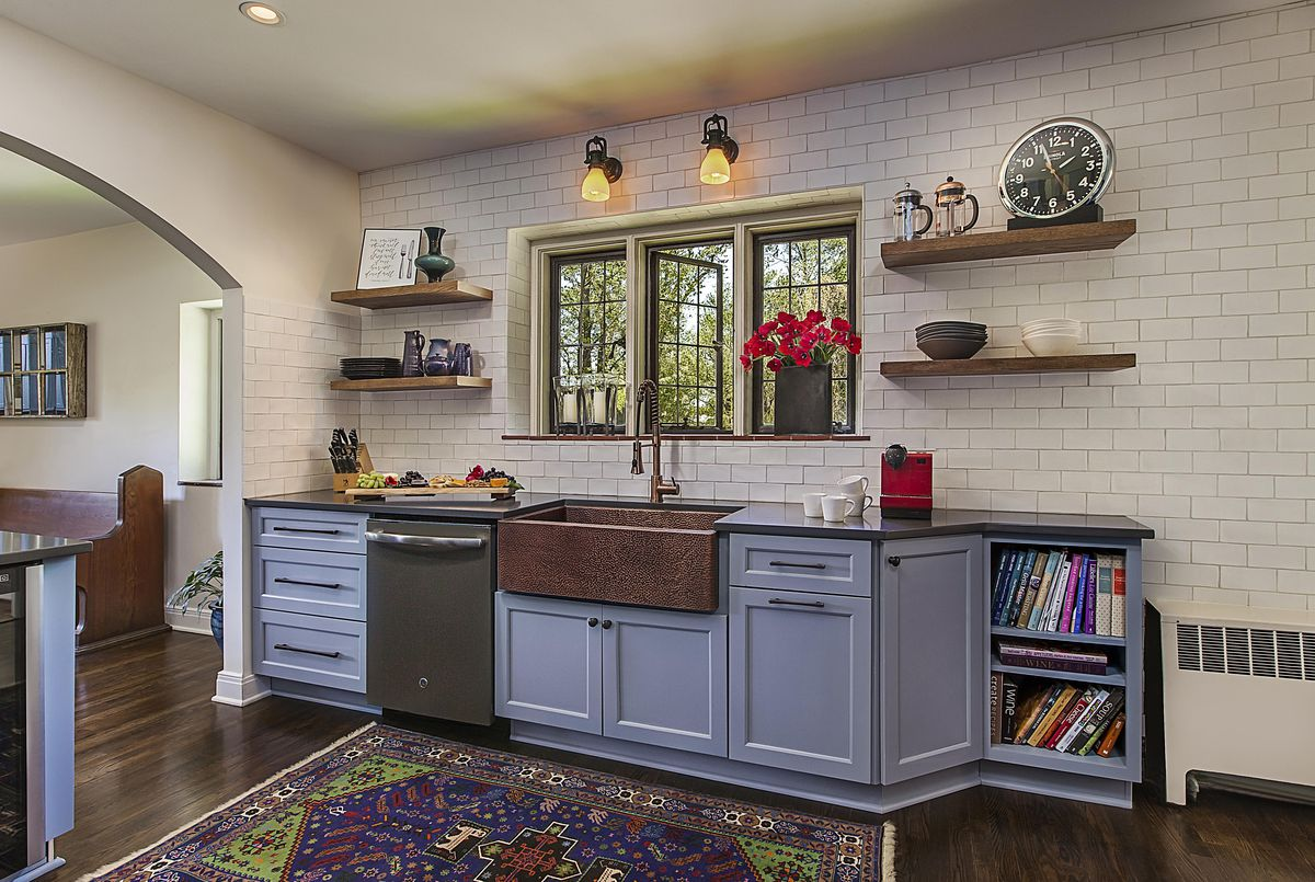 The kitchen has white tiles covering one wall, a big copper sink, and blue cabinets. There's some hovering wood shelves.